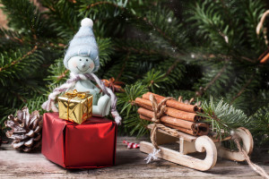Christmas card with snowman, sled, cinnamon and christmas gifts over old wooden background