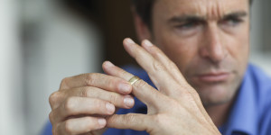 Mature man toying with gold wedding ring on finger